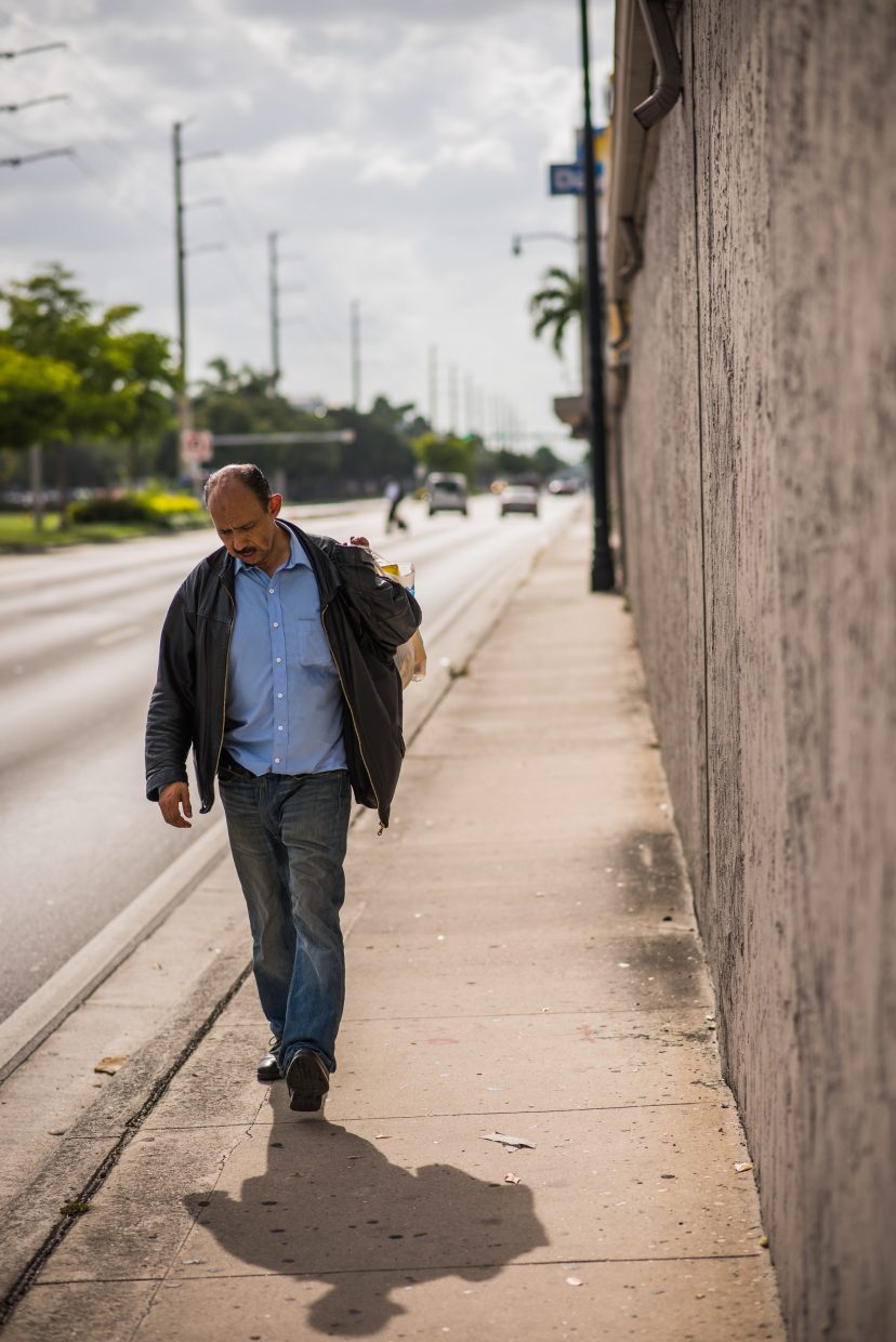A man walks along a Miami sidewalk prior to the storm's arrival. (Photo by Tyler Tomasello)