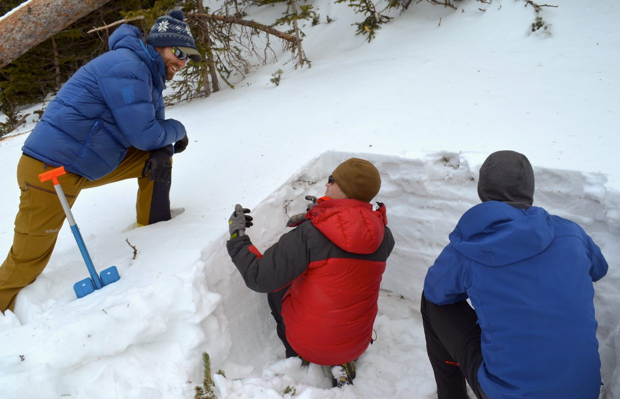 Colorado Mountain School guide and instructor Ben Markhart chats with student Nate Landry as Landry and fellow student Aaron Oakley check snow firmness in a snow pit.