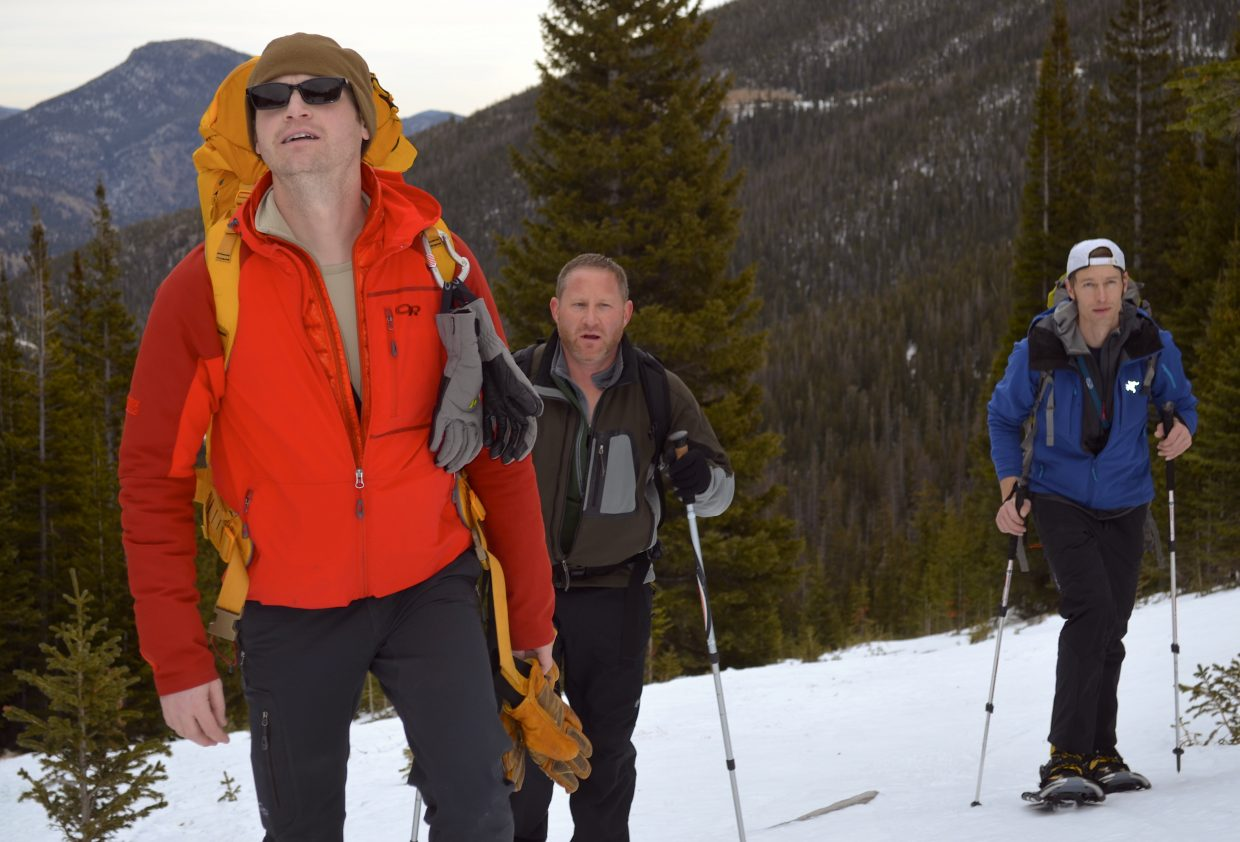 Colorado Mountain School students Nate Landry (left) Jeff Harris (center) and Aaron Oakley (right) stare up at the high peaks of Rocky Mountain National Park as they snowshoe up through Hidden Valley as part of their AIARE Level 1 course.