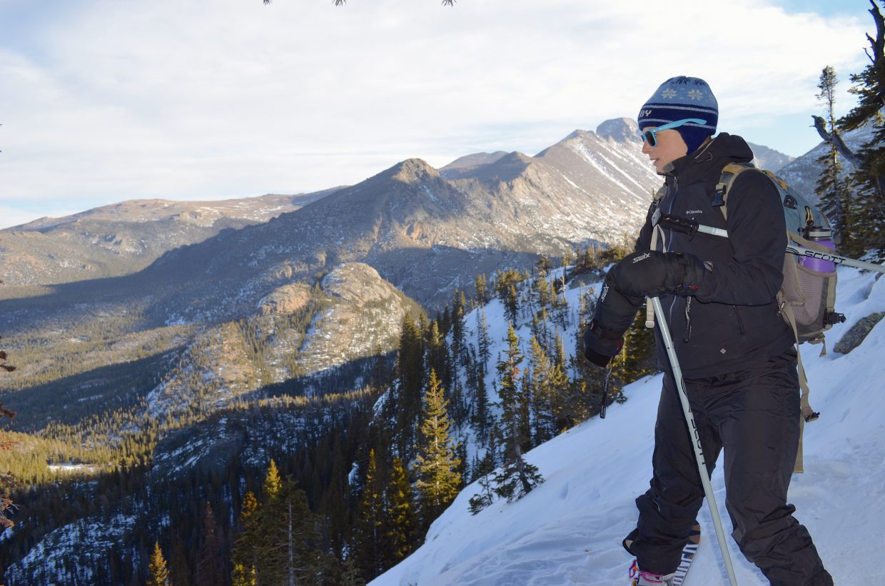 A Colorado Mountain School AIARE Level 1 student pauses briefly on a mountainside high above Bear Lake in Rocky Mountain National Park as she works her way down from Lake Haiyaha. Longs Peak is visible in the distance.