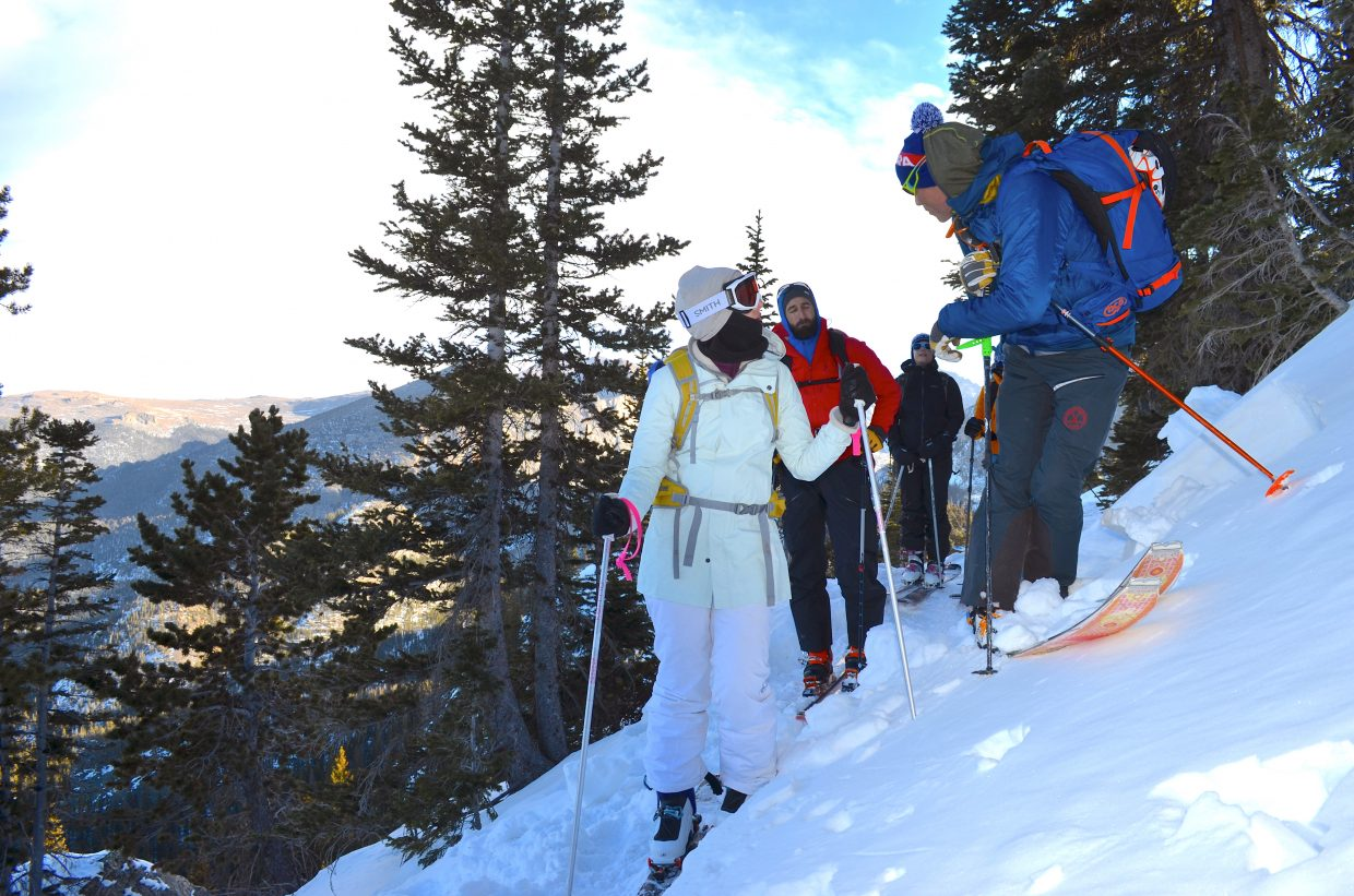 Joey Thompson (right), lead instructor for CMS's AIARE Level 1 Course, looks back over his shoulder as he speaks to his students about backcountry avalanche hazards and terrain selection while traversing a steep slope in Rocky Mountain National Park.