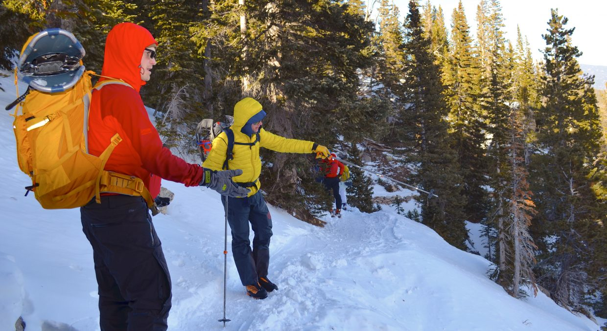 AIARE instructor and former Rocky Mountain National Park Ranger Adam Baxter (yellow coat) points out some potential avalanche terrain while discussing backcountry traveling with students near Lake Haiyaha.