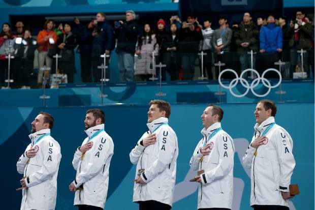 Gold medal winners from left: United States' curlers Joe Polo, John Landsteiner, Matt Hamilton, Tyler George, John Shuster and captain Phill Drobnick sing the national anthem during the men's curling venue ceremony at the 2018 Winter Olympics in Gangneung, South Korea, Saturday, Feb. 24, 2018. (AP Photo/Natacha Pisarenko)