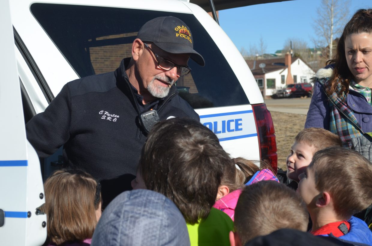 Granby Police Officer and East Grand School District School Resource Officer Craig Parten shows local students around his police vehicle during the Career on Wheels event Tuesday morning.