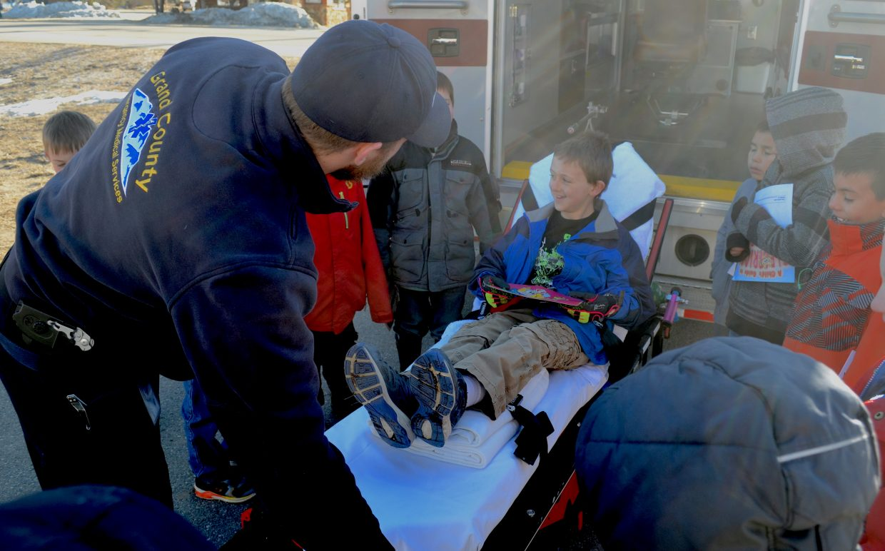 Grand County EMS Paramedic Erik Campbell (left) leans over a gurney holding a student from Granby Elementary School during the school's Career on Wheels event earlier this week.
