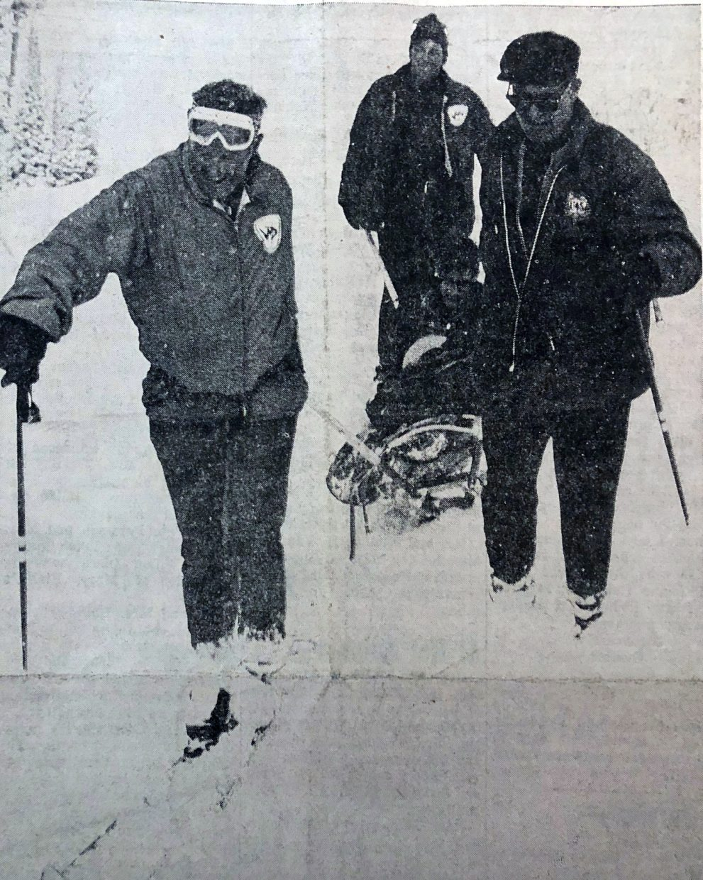 RESCUE TEAM — Albert Hendricks, 17, of Valhalla, N.Y., is brought down from the Rollins Pass area Tuesday, March 19, 1968 by a rescue team. Ted Birdsill, left, and C.B. Jensen, right, of the Winter Park Ski Area are joined by Wait Werner, center, a ranger with the Fraser Ranger District, to pull Hendricks, seated, from the pass. Hendricks and two companions had spent three nights out, while attempting to hike over Rollins Pass from East Portal to Winter Park. (Sky-Hi News, 1968, by Bob Davis)