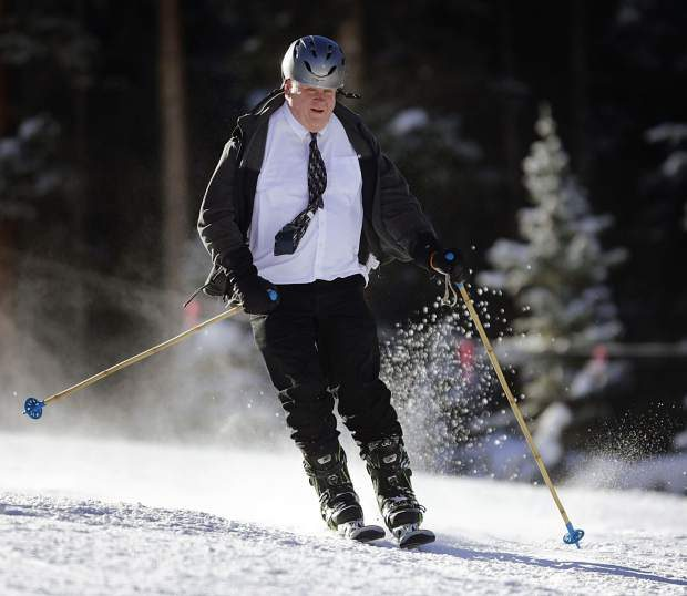 A skier dressed in full-on business attire makes one of the first runs of the season on opening day at Arapahoe Basin Ski Area on Friday.