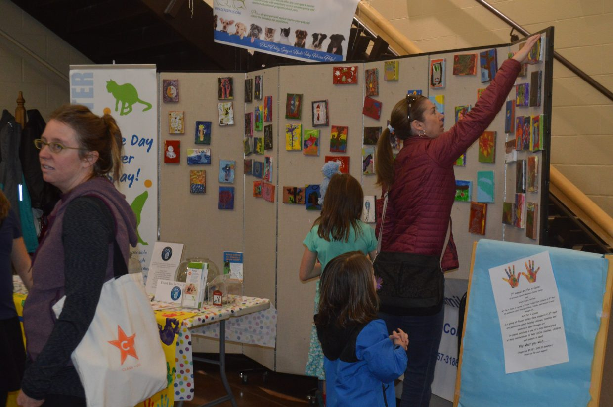Megan Henderson looks for her daughter Finley's painting at the Art For a Cause booth. Finley, 6, participated for the first time this year because she loves creating.