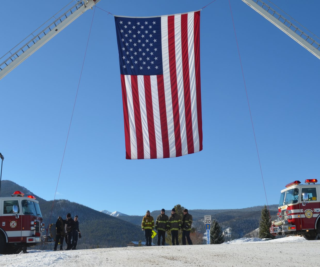 Local firefighters stand underneath a massive flag draped between two fire engines at the entrance to YMCA Snow Mountain Ranch where Monday's Veterans Day ceremonies were held.