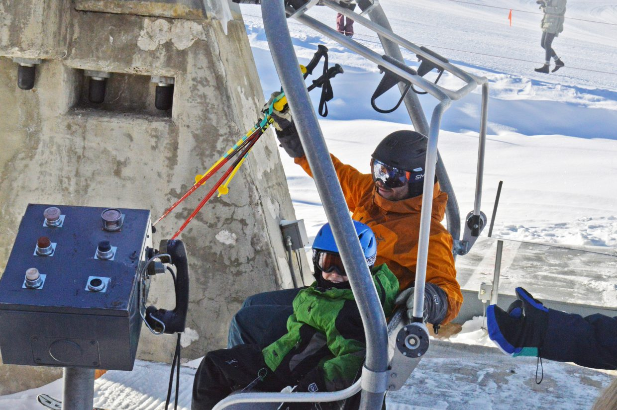 Kevin McKinney and his son, Henry, happily claim the second chair on opening day at Ski Granby Ranch.
