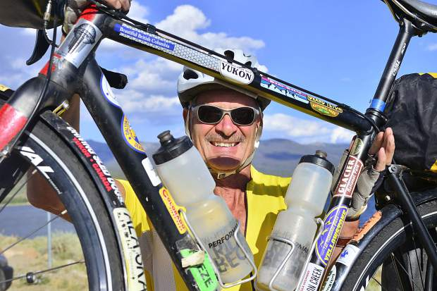 Mike Darrah hoists his bike into the air to show off some of the stickers he picked up during his long-distance bike trips.